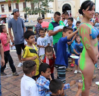 Niños pintan a una modelo desnuda